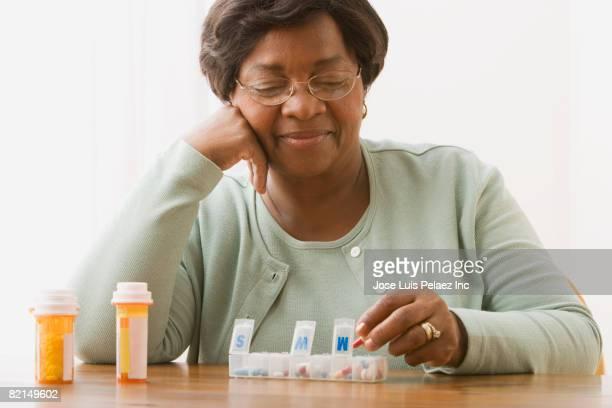 Senior African woman taking medication