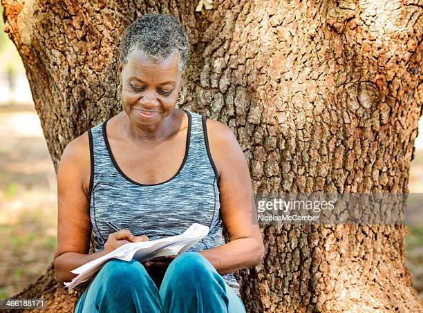 Senior African woman writing outdoors