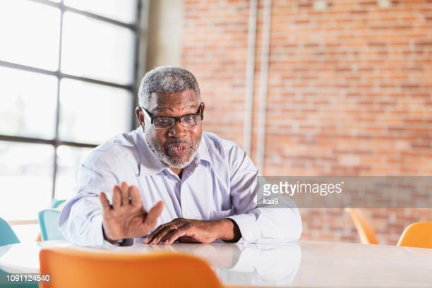Senior African-American businessman, talking to viewer