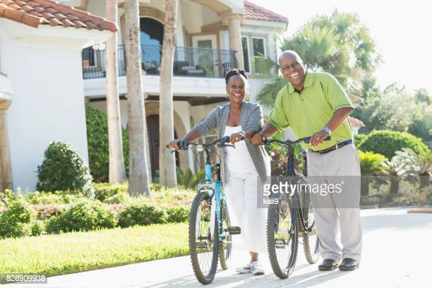 senior african-american couple riding bicycles - early retirement stock pictures, royalty-free photos & images