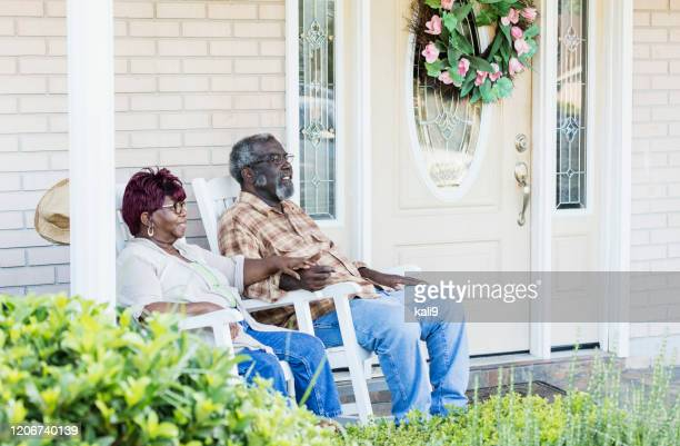 senior african-american couple together on front porch - rocking chair stock pictures, royalty-free photos & images