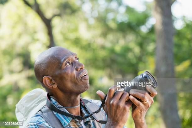 Senior African-American man hiking, with camera