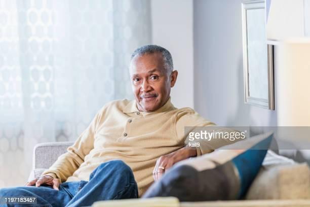 uomo afro-americano anziano seduto a casa - 65 69 anni foto e immagini stock