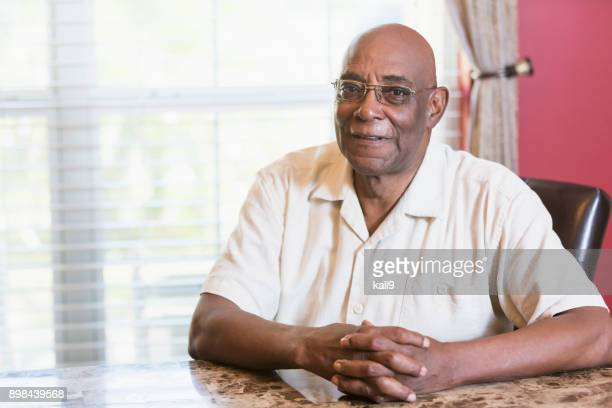 Senior African-American man sitting at table by window