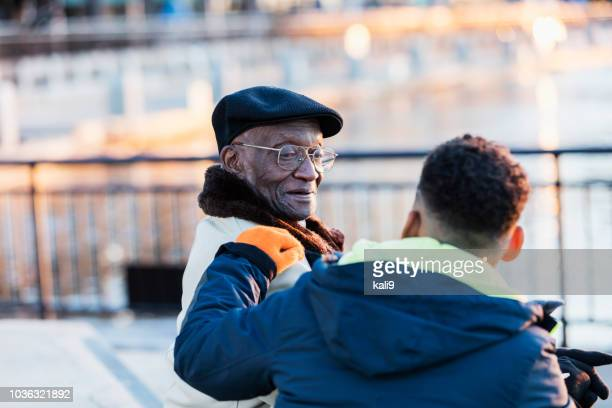 Senior African-American man sitting with great grandson
