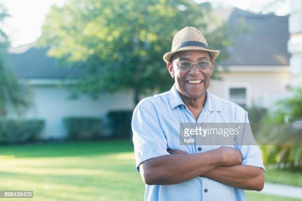 senior african-american man standing in front yard - black hat stock pictures, royalty-free photos & images