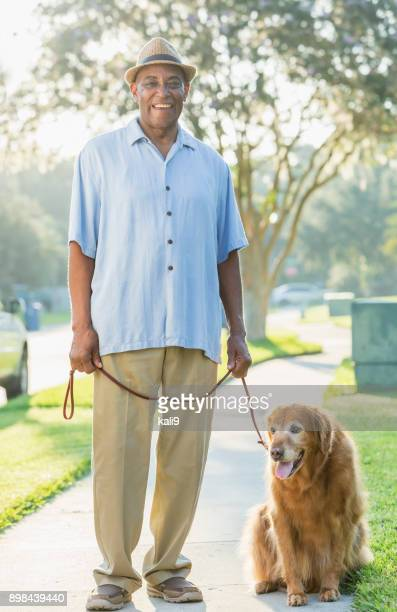 senior african-american man walking his dog - dog walker stock photos and pictures