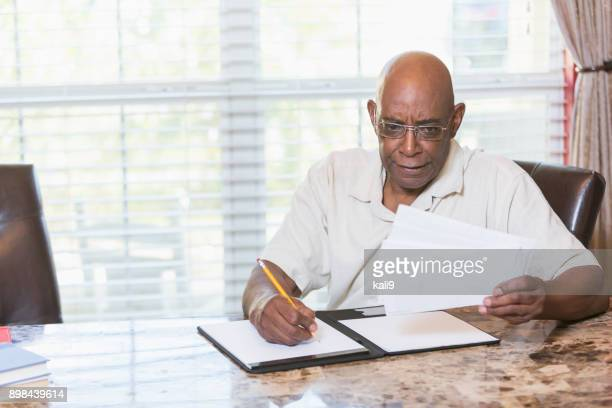 senior african-american paying bills - african american ethnicity imagens e fotografias de stock