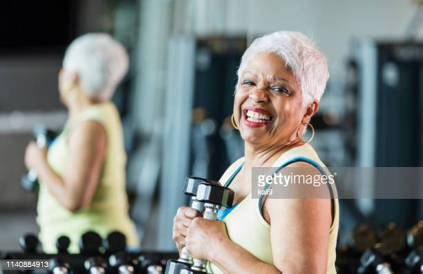 senior african-american woman at gym lifting dumbbells - hand weight stock pictures, royalty-free photos & images