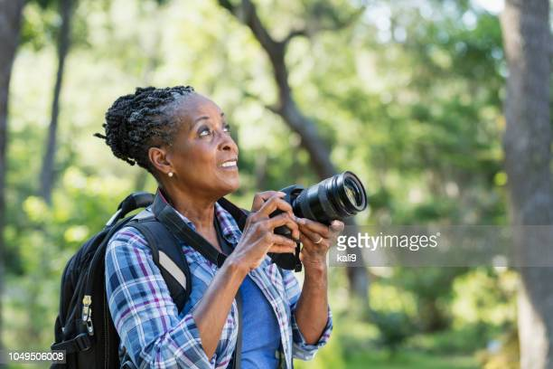 senior african-american woman hiking, with camera - hobby foto e immagini stock