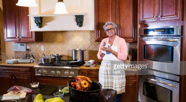 senior african-american woman in kitchen cooking - images of fat black women stock photos and pictures