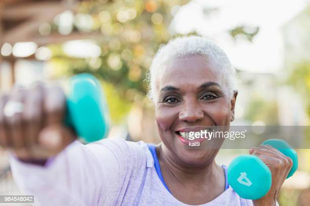 senior african-american woman lifting hand weights - hand weight stock pictures, royalty-free photos & images