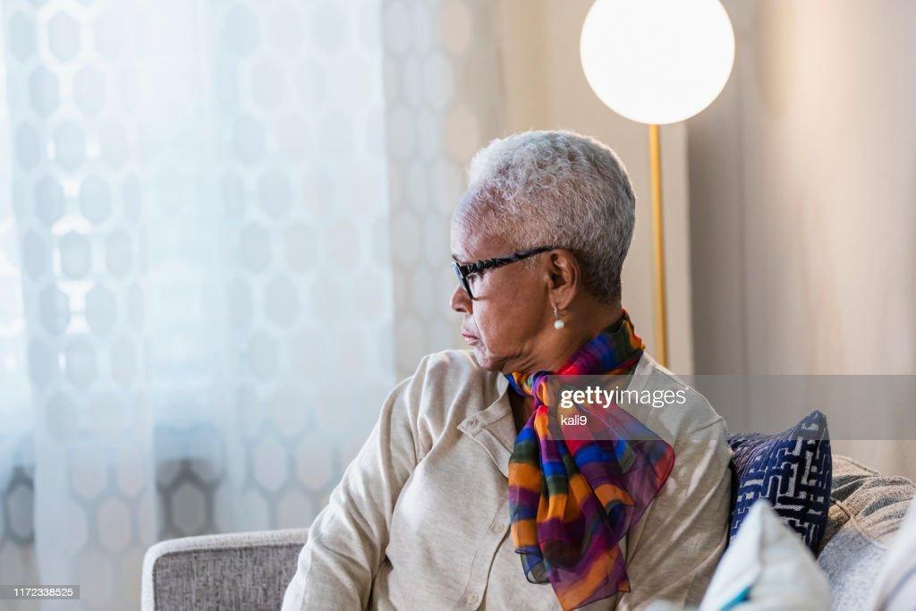 Senior African-American woman looking through window : Stock Photo