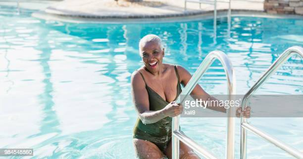 senior african-american woman on swimming pool ladder - old woman in swimsuit stock pictures, royalty-free photos & images