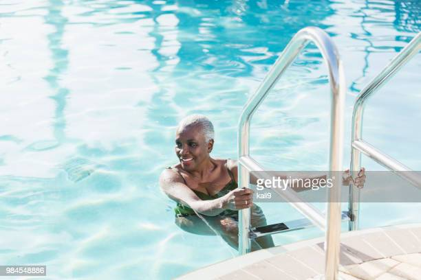 senior african-american woman on swimming pool ladder - swimming stock pictures, royalty-free photos & images
