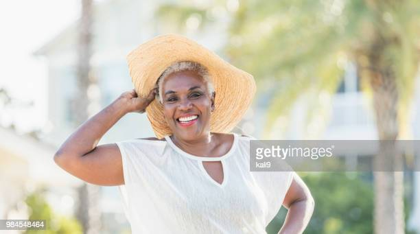 senior african-american woman on tropical vacation - wide brim stock pictures, royalty-free photos & images