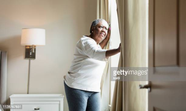 senior african-american woman opening curtain - fat old women stock pictures, royalty-free photos & images