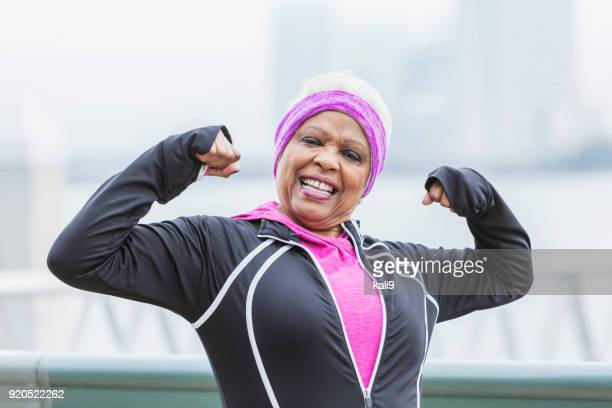 senior african-american woman outdoors, flexing muscles - flexing muscles stock pictures, royalty-free photos & images