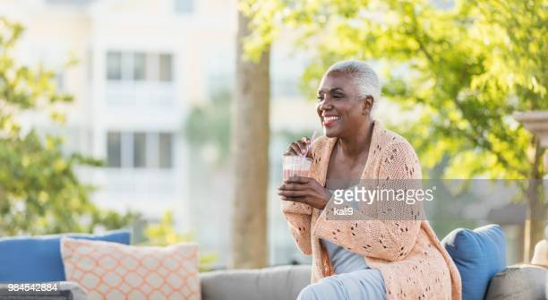 senior african-american woman relaxing on patio - milkshake stock photos and pictures