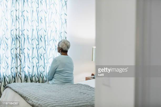 senior african-american woman sitting on bed, thinking - loneliness stock pictures, royalty-free photos & images