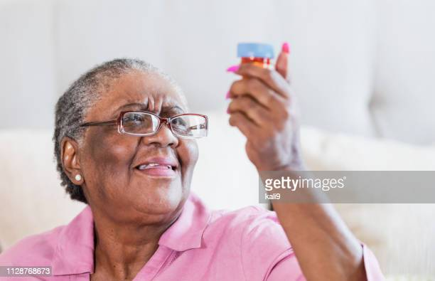 senior african-american woman with prescription bottle - short hair for fat women stock pictures, royalty-free photos & images