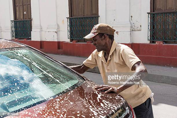 Senior Afro Caribbean man washing a tourist's car outside the Santa Rosalia Restaurant While tourist have lunch this man washes their autos for a tip...