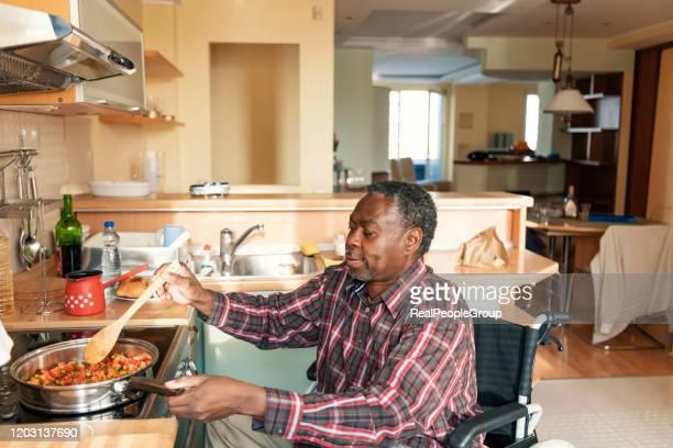 l'afro-americano senior in sedia a rotelle sta preparando un pranzo a casa - accessibilità foto e immagini stock