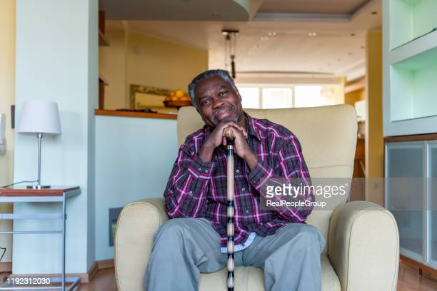 senior afro-american is relaxing in armchair at home - walking cane stock pictures, royalty-free photos & images