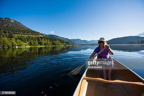 Senior aged woman canoeing on a pristine lake