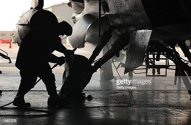 S Senior Airman Ryan Fletcher a dedicated crew chief 31st Aircraft Maintenance Squadron hoses down an F16's main landing gear wheel wells as part of...