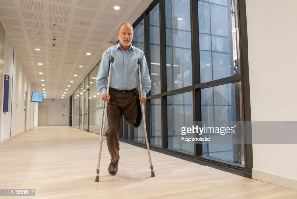 senior amputee man walking through the hospital's corridor using crutches - hispanolistic stock photos and pictures