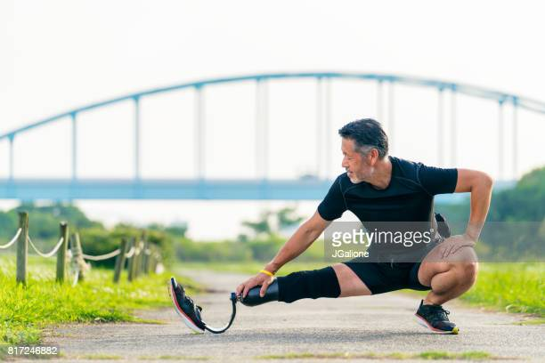senior amputee stretching before a run - artificial limb stock photos and pictures