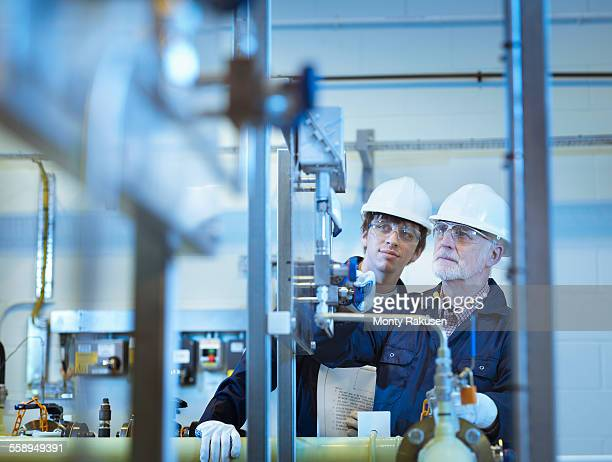 Senior and apprentice engineers working in power station