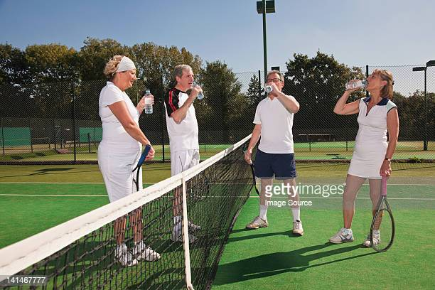 Senior and mature adults enjoying drink on tennis court