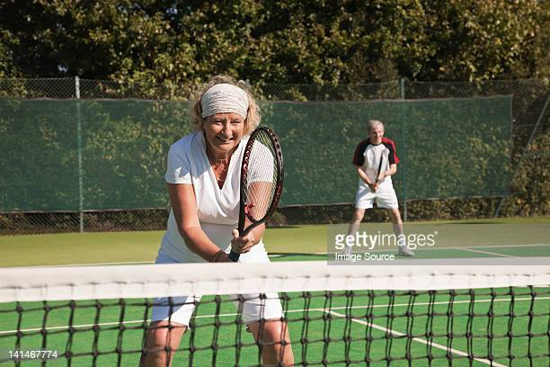 Senior and mature adults playing tennis