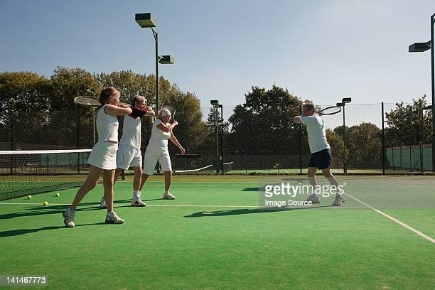 Senior and mature adults practising tennis