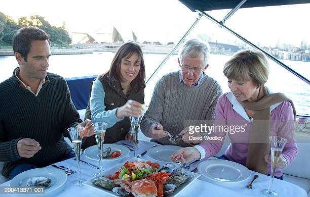 Senior and mature couple eating seafood on yacht, smiling