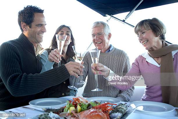 Senior and mature couple having meal on yacht, raising drinks, smiling