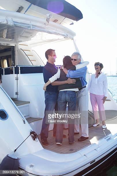 Senior and mature couples on yacht, senior man embracing woman
