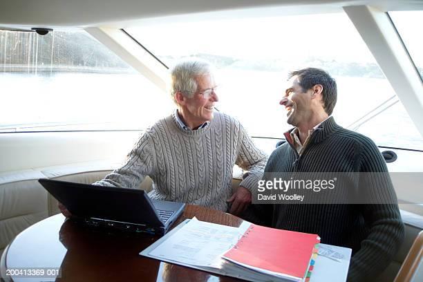 Senior UND Älterer Mann sitzt am Tisch auf yacht, Lächeln
