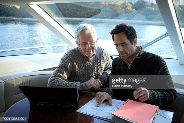 Senior and mature man sitting on yacht looking at file together