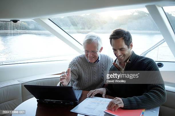 Senior UND Älterer Mann sitzt auf yacht mit laptop und Lächeln