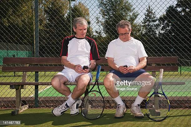 Senior and mature men texting on tennis court