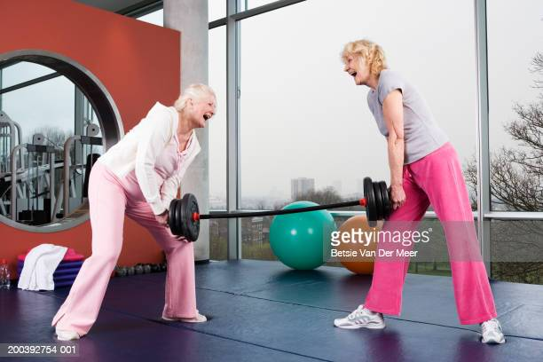senior and mature woman lifting weight together in gym, smiling - oggetti pesanti foto e immagini stock