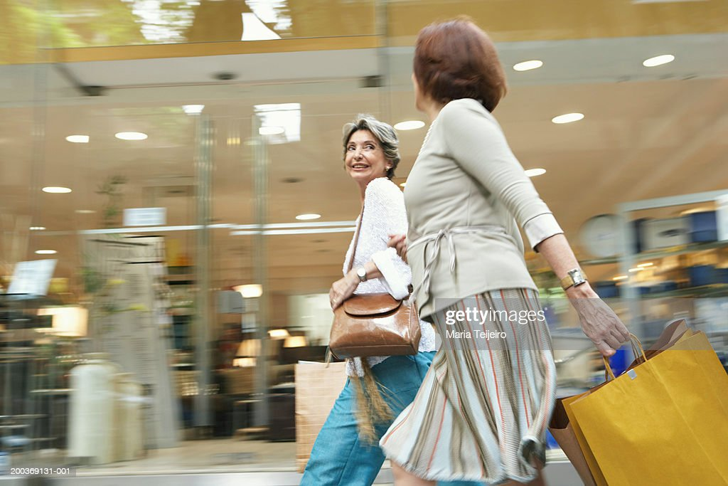 Senior and mature woman  walking past shop carrying bags : Stock Photo