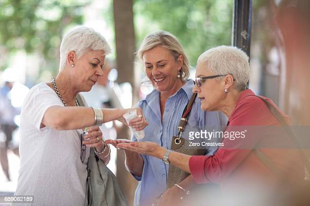 senior and mature women sharing hand cream in city - hand cream stock photos and pictures