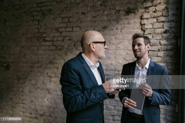 senior and mid-adult businessman having a meeting - junior level stock pictures, royalty-free photos & images