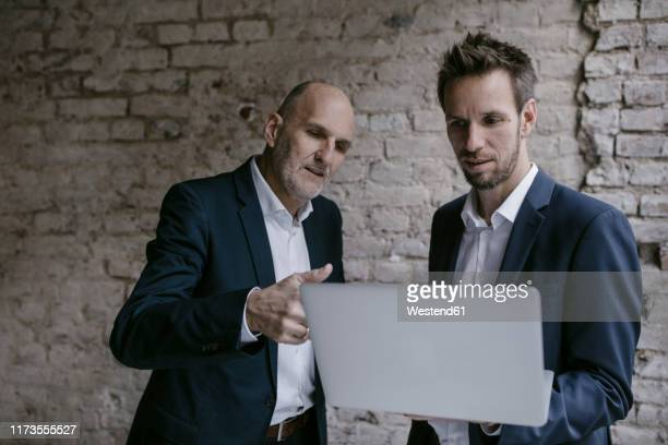 senior and mid-adult businessman having a meeting using laptop - 後任 ストックフォトと画像