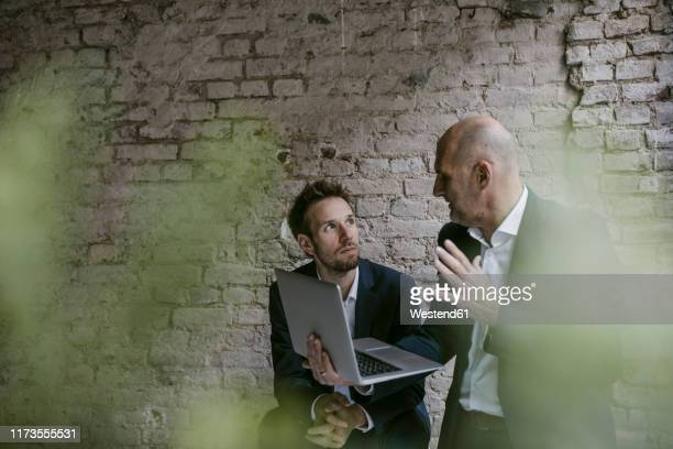 senior and mid-adult businessman having a meeting using laptop - successor stock pictures, royalty-free photos & images