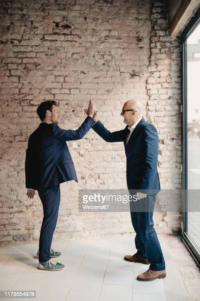 senior and mid-adult businessman high fiving - successor stock pictures, royalty-free photos & images
